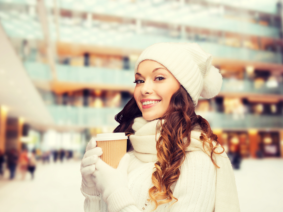 happiness, winter holidays, christmas, beverages and people concept - smiling young woman in white hat and mittens with coffee cup over shopping center background