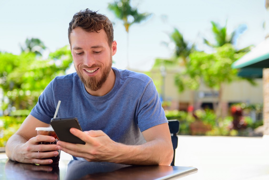 Smartphone man sms texting drinking cold coffee drink at outdoor